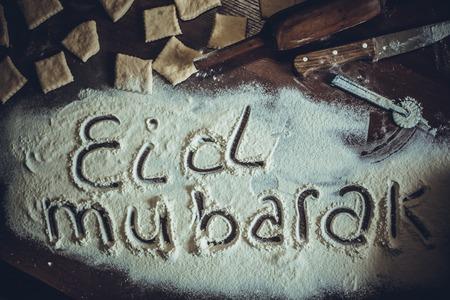 Eid Mubarak phrase written on flour. Preparation process of traditional arabic muslim cooks