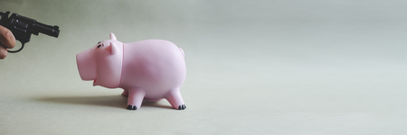 A man is going to take out his broke piggy bank with a loaded pistol.