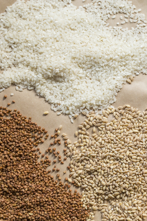 Raw cereals, buckwheat, barley, rice on brown paper background