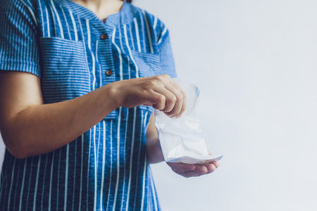 Young woman holding sanitary napkins. Period days concept showing feminine menstrual cycle. Фото со стока