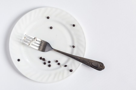 Empty dirty white plate and fork on the white background. Dirty plate with pieces and crumbs dessert. Copy space for text.