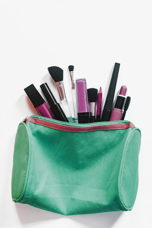 Beauty concept. Womens make-up bag with beauty products. Cosmetics and brushes on white background, View from above.