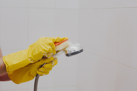 Woman in rubber gloves cleaning the shower head. Housemaid washing metallic head of the shower. Housewife cleaning up in the bathroom.