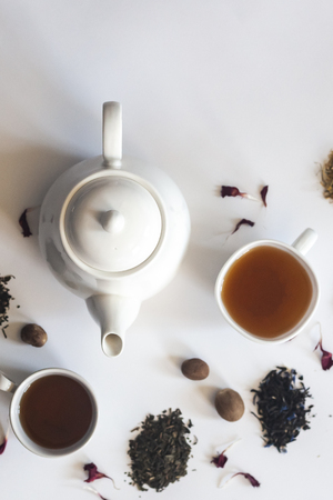 Tea set with white ceramic tea pot, dried rose flowers and other tea ingredients on the white. Flat lay view of various dried teas and teapot. View from above. Copy space Stock Photo