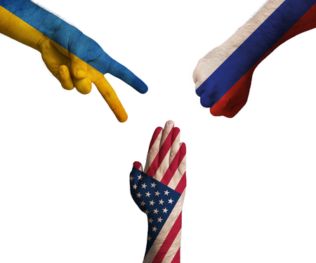 hands decorated in flags of Ukraine, United States of America and Russian Federation showing Scissors, paper, stone - symbolizing the political games between them