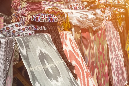 Traditional Uzbek asian silk. Multicolored silk textile materials fluttering on wind. Trading with silk fabric materials in the open air shop, store, market. Colorful traditional uzbek xonatlas hon atlas textile fabric trading point