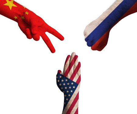 hands decorated in flags of China, United States of America and Russian Federation showing Scissors, paper, stone - symbolizing the difficult political relationship