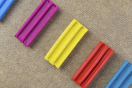 Colorful piece of plasticine or modeling clay on wooden background. Rainbow set for children play.