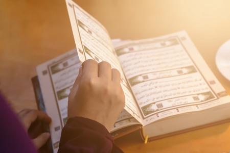 正在祈祷的年轻穆斯林妇女。中东女孩祈祷和阅读神圣的可兰经。一个穆斯林妇女在家里学习古兰经