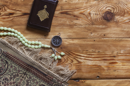 Traditional muslim prayer set bundle. Praying carpet, rosary beads, little version of the Holy Quran and qibla compass on wooden background. Copy Space 版權商用圖片
