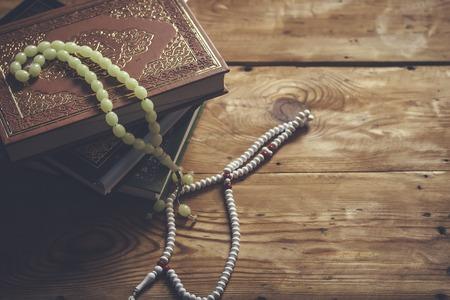 Le Coran. Livre sacré des musulmans Coran. Le Saint Coran avec des perles de prière sur fond de bois. Espace de copie