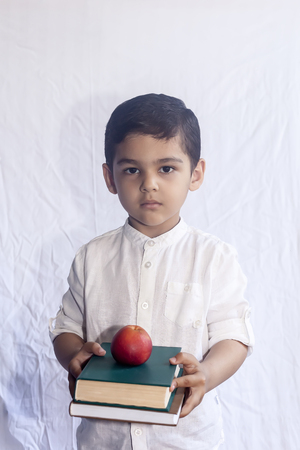 Back to school concept. Cute middle eastern boy holding a stack of books against the white background. Portrait of Central Asian kid preparing to go to school. Vetical photo