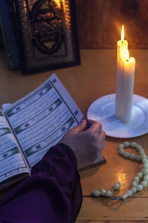 Praying young muslim woman. Middle eastern girl praying and reading the holy Quran. Muslim woman studying The Quran at home