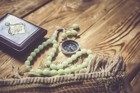 Traditional muslim prayer set bundle. Praying carpet, rosary beads, little version of the Holy Quran and qibla compass on wooden background. Copy Space Stock fotó