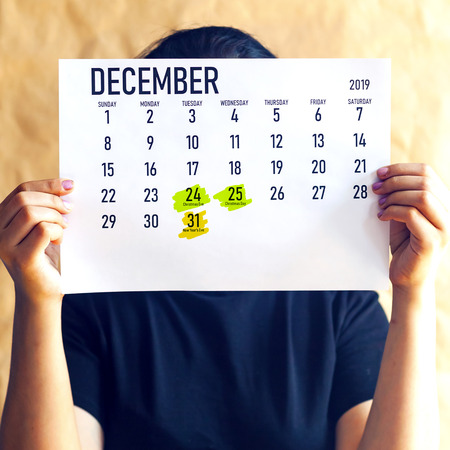 Woman holding December Calendar with marked holidays. Winter holidays concept Stock fotó