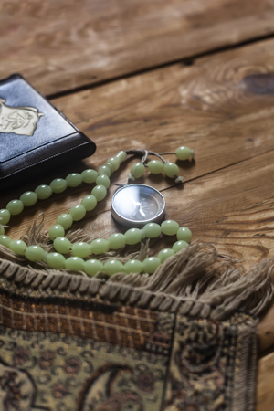 Traditional muslim prayer set bundle. Praying carpet, rosary beads, little version of the Holy Quran and qibla compass on wooden background. Copy Space