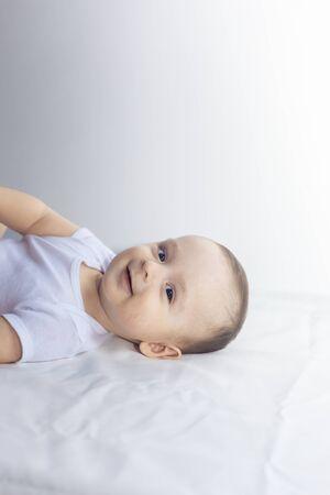 6개월 아기가 하얀 침구에서 즐거운 시간을 보내고 있습니다. 침대에 누워 귀여운 아기입니다. 가족, 새로운 삶, 어린 시절 개념.