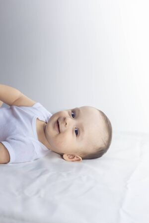Bebé de 6 meses divirtiéndose en ropa de cama blanca. Lindo bebé acostado en la cama. Familia, nueva vida, concepción infantil.