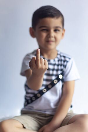 Six-year-old boy showing middle finger. 6-year kid hand gesturing with his middle finger. Obscene sign for a negative attitude.