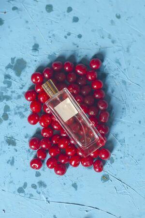 Cherries and perfume glass bottle. Pile of ripe cherries and parfume glass bottle on blue background. Fresh organic berries. Healthy fruit Reklamní fotografie - 124858438