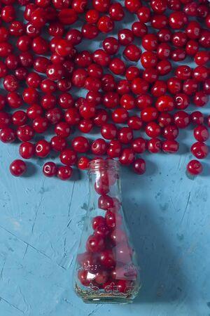 Pile of ripe cherries and glass bottle on blue background. Fresh organic berries. Healthy fruit Reklamní fotografie - 124858562