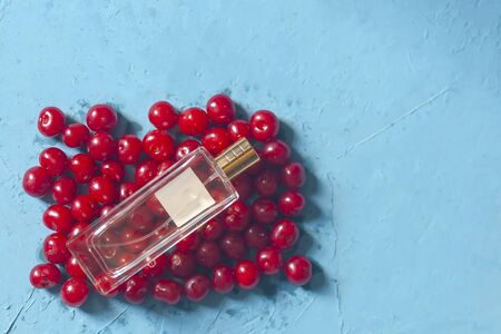 Cherries and perfume glass bottle. Pile of ripe cherries and parfume glass bottle on blue background. Fresh organic berries. Healthy fruit Reklamní fotografie - 124858585