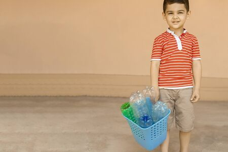 Plastic pollution. Little boy collected plastic bottles and holding recycling bin. Copy space