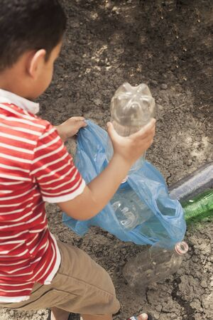 Plastic pollution on land. Little boy collecting plastic bottles. Kid carry garbage bag. Copy space