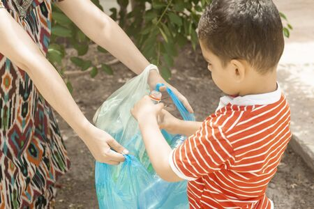 Mother and son collecting plastic bottles. Family carry garbage bag. Plastic pollution on land. Copy space Imagens