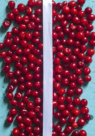 Cherry background with white ribbon. Fresh organic berries. Pile of ripe cherries. Healthy fruit Reklamní fotografie - 124859018