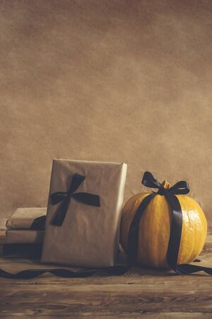 Halloween gift box with ribbons and pumpkins on wooden table. Holiday, Birthday, Halloween party celebration concept.