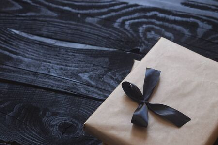 Halloween gift box with black ribbon on dark wooden table. Holiday, Birthday, Celebration concept.