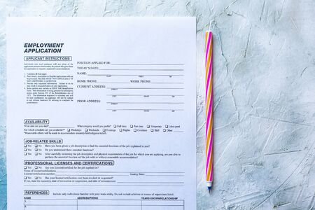 Standard Application for Employment. HR, Hiring, Applying concept. Job Application form. Top view. Multicolored paper clips and pen. Stock Photo
