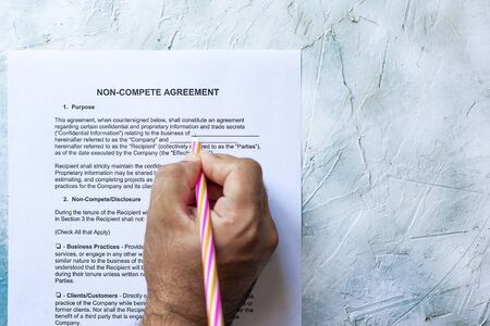 Person filling Non-Compete Agreement Form. View from above
