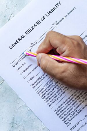Person filling General Release of Liability form paper on bright background Foto de archivo