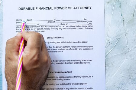 Person filling Durable financial power of attorney form on bright background