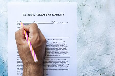 Person filling General Release of Liability form paper on bright background