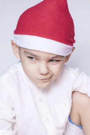 Annoyed Christmas Boy in Santa Hat. A little kid making a funny annoyed face. Christmas Boy in Santa Hat. A really serious and handsome kid. Boring Christmas holidays Imagens