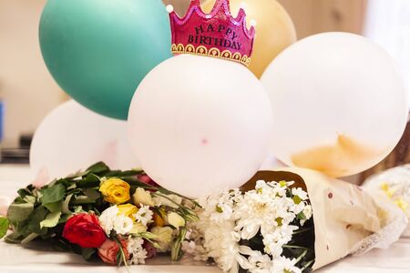 First birthday concept. Birthday decorations ready to party. Bouquet of flowers and air balloons with a crown for the little princess