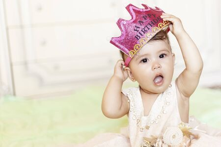 First birthday. Little cheerful baby girl with crown celebrating her first birthday party. A funny baby girl dressed as a princess