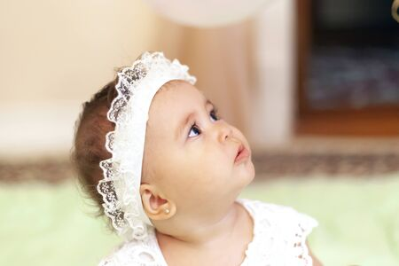 Portrait of the cute little princess in a white dress. Little baby girl looking up with adorable facial expression. First birthday.