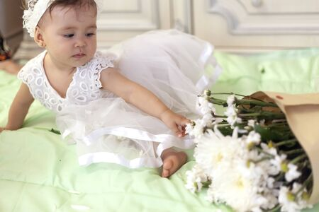 Baby girl in white dress taking a beautiful single white flower. Little princess playing with bouquet of flowers at her first birthday