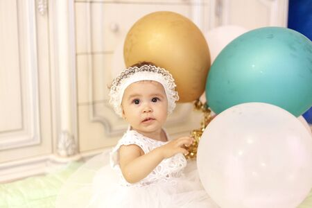 Little princess in white dress playing with air balloons. First birthday. Banco de Imagens