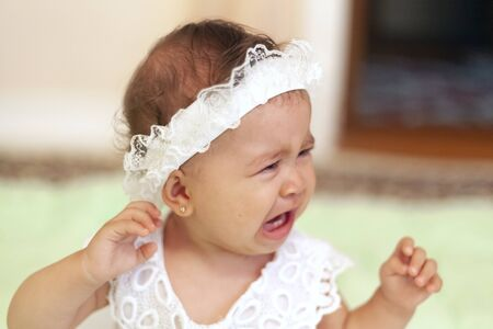 Crying baby girl. Portrait of the cute little princess in a white dress. Little baby girl crying. Facial expression