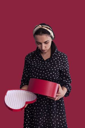 Female disappointed with gift. House wife not satisfied with present. Young woman opening a red gift box and feel unhappy.