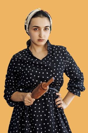 Angry wife waiting for her husband. Aggressive young middle-eastern woman holding dough rolling pin