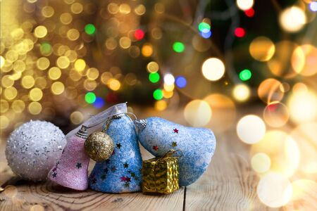 Christmas decor with bright bokeh lights. Magic Winter at Christmas Time. Xmas decoration with Christmas toys and balls on vintage wooden desk. Advent Christmas Decorations. Copy space for text and ad