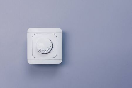 Dimmer Light Switch. Electrician switch. White rolling electricity switch on bright wall