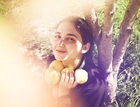 Porträt der schönen nahöstlichen Frau im Apfelgarten. Junge Frau, die mit frisch gepflückten Herbstapfelfrüchten aufwirft. Porträt der Frau an der Natur. Essen frischen Apfel. Herbstporträt der Apfelfrau Standard-Bild