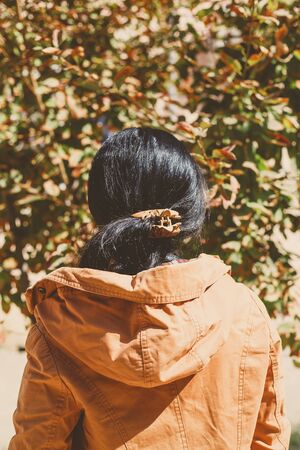 Autumn woman. Fall season concept. Woman watching autumn tree leaves falling. View from behind. Autumn or fall woman. Sunny autumn weather at outdoors.